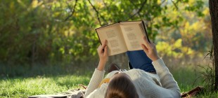 Woman reading book outdoors